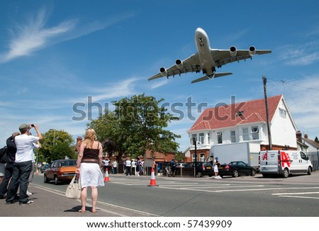 FARNBOROUGH INTERNATIONAL AIRSHOW, UK - JULY 19: Massive Airbus A380 aircraft on landing approach over local suburban street. Farnborough Airshow - July 19, 2010. Hampshire, UK. - stock photo