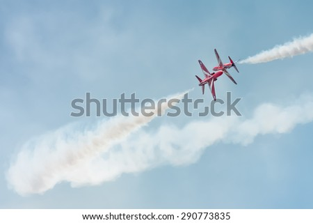 FARNBOROUGH, UK - JULY 18: Close pass by The Red Arrows formation aerobatic display team in the skies over Farnborough, UK on July 18, 2014 - stock photo