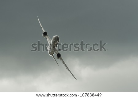 FARNBOROUGH, UK - JULY 11: The newly unveiled Boeing 787 Dreamliner in Qatar Airways livery banking steeply through dark clouds during the international airshow at Farnborough, UK on July 11, 2012 - stock photo
