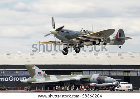 FARNBOROUGH, UK - JULY 24: WW2 Spitfire coming into land with XH558 Vulcan bomber in the background. July 24 2010, Farnborough Airshow, UK.