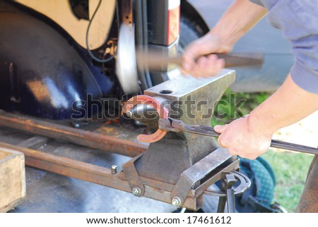 Farrier or blacksmith working on a hot horseshoe with motion blur - stock photo