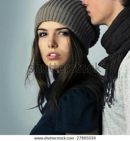 Fascinating woman looking to the camera next to young attractive man kissing her on the head