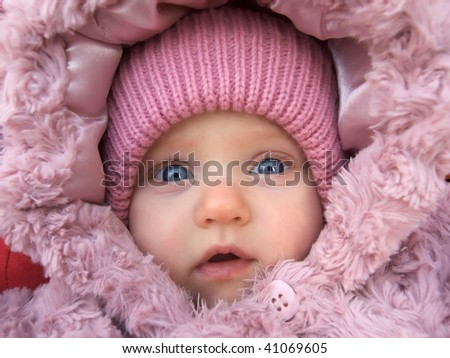 Fase of baby girl in a winter hood - stock photo