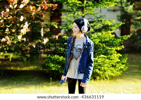 Fashion adorable school aged kid girl with headphones dancing and listnening music outdoors in the park - stock photo