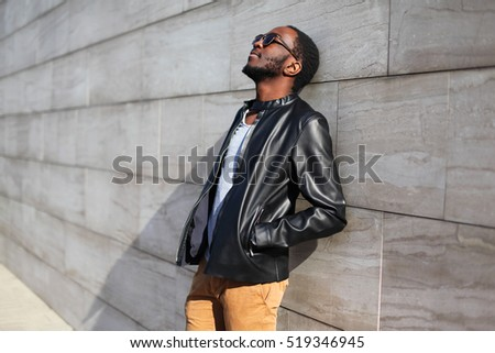 Fashion african man relaxing in the city over gray background