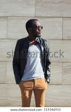 Fashion african man wearing a sunglasses and black rock leather jacket over textured background evening in city