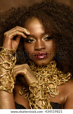 Fashion African or American woman with black curly hair, gold makeup and accessories posing holding hands near face - stock photo