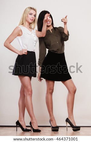 Fashion and advertisement concept. Two women caucasian and african in full length pointing copy space, studio shot