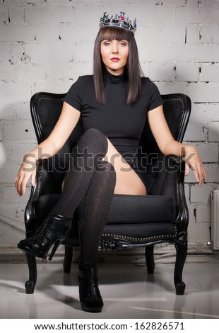 fashion and glamour concept - sexy woman in crown and black dress sitting in chair - stock photo