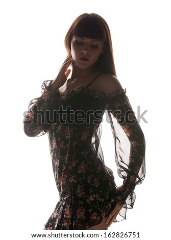 fashion and glamour concept - silhouette backlight picture of woman in black dress - stock photo