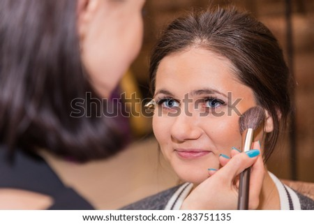 Fashion and make-up. Makeup artist at work. Makeup artist applies cosmetics to the face of the model. Powder, brush, make-up tools. Preparing for the exit before the fashion show. - stock photo