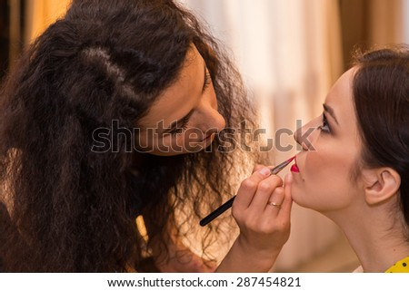 Fashion and make-up. Makeup artist at work. Makeup artist applies cosmetics to the face of the model. Powder, brush, make-up tools. Preparing for the exit before the fashion show.