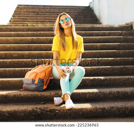 Fashion and people concept - lifestyle portrait stylish pretty girl in sunglasses posing in the city, street fashion - stock photo