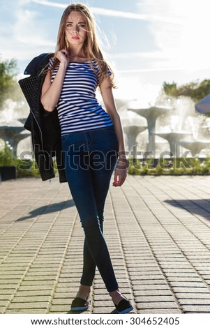 Fashion and people concept. Woman  in denim trousers casual style outdoor against city fountain