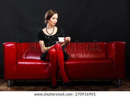 Fashion and relaxation concept. Woman retro style in full length. Elegant lady holding coffee tea cup hot drink sitting on red sofa, indoor - stock photo