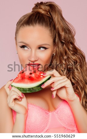 Fashion and sexy young woman holding slice of watermelon isolated on pink