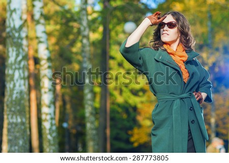 Fashion and Style Concept and Ideas: Good Looking Caucasian Female Model in Green Coat Posing with Sunglasses in Autumn Forest. Horizontal Image Orientation - stock photo