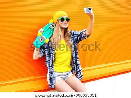 Fashion and technology concept - stylish young girl in colorful clothes with skateboard having fun makes self-portrait on the smartphone against the orange wall - stock photo