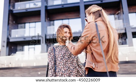 Fashion and the city. Two stylish girls are walking on the street. One is wearing leather jacket. Another -motley dress. - stock photo