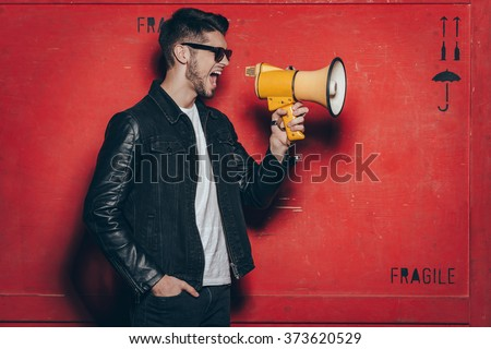 Fashion announcement. Side view of handsome young man in sunglasses holding megaphone and keeping mouth open while standing against red background - stock photo