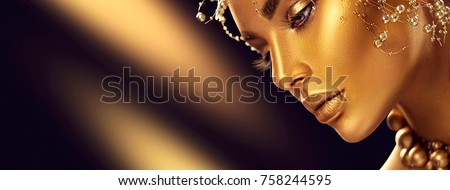 Fashion art Golden skin Woman face portrait closeup. Gold jewellery, jewelry and accessories. Beauty gold eyes, Lips and Skin and hair. Model girl with holiday golden Glamour shiny professional makeup