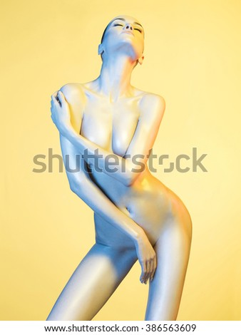 Fashion art photo of elegant nude model in the light colored spotlights