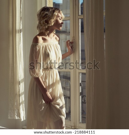 Fashion art portrait of beautiful blonde at the window - stock photo