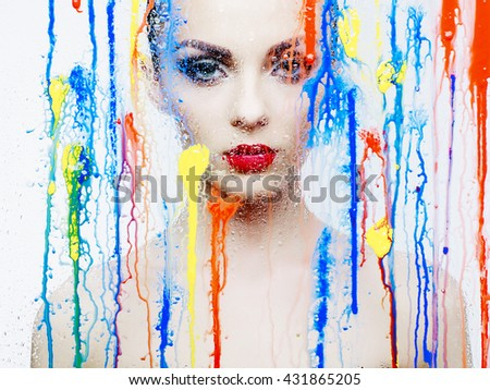 Fashion art studio photo of beautiful model through the glass with bright colors - stock photo