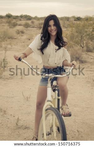 Fashion art style photo ( soft and grainy ) of boho Californian girl riding beach bike. - stock photo