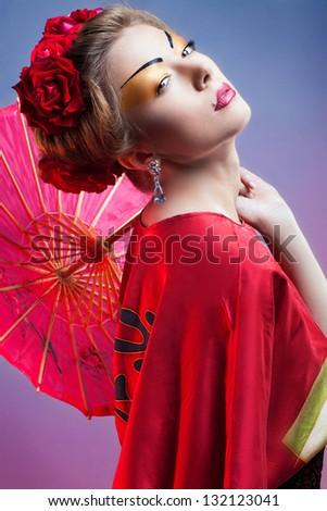 Fashion asian woman wearing traditional japanese red kimono  with umbrella, studio shot.  Geisha - stock photo