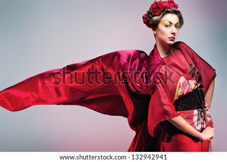 Fashion asian woman wearing traditional japanese red kimono with umbrella, studio shot. Geisha