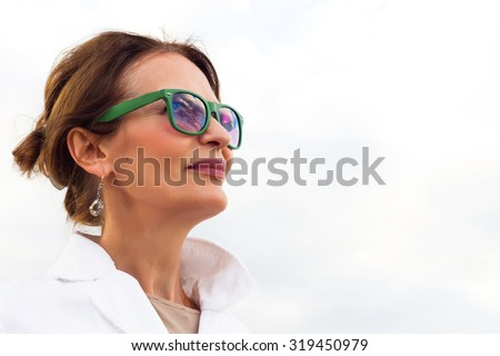 Fashion autumn close up portrait of Happy mature woman looking in to the sky,isolated on white.Looking forward,side view. Brunette woman wearing white jacket and green sunglasses,tanned,fresh make up - stock photo