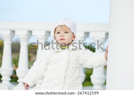 fashion baby girl is wearing fur coat - stock photo