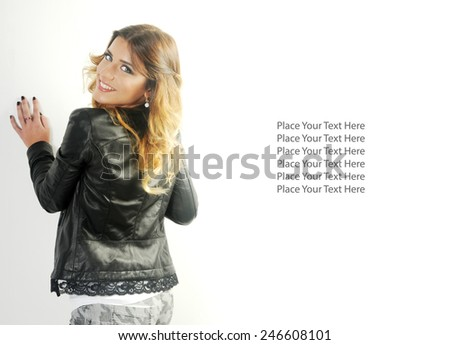 fashion background with a portrait of a Young teen girl leaning towards the White wall with her back towards the camera and looking over her shoulder smiling at the camera - stock photo