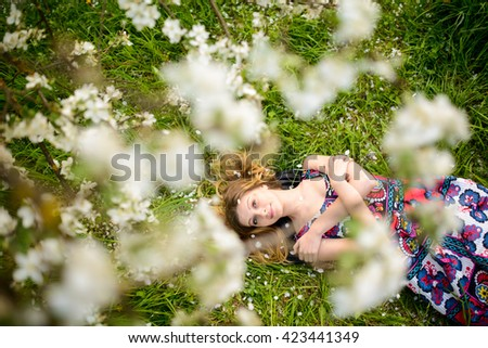 fashion beautiful blonde woman in spring blossoming garden of Apple trees - stock photo