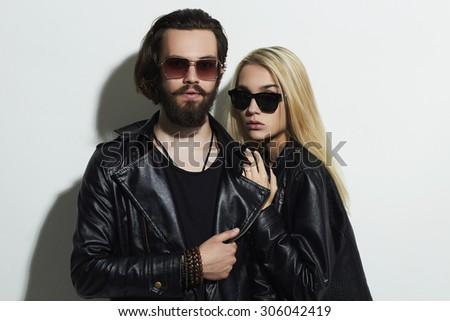 fashion beautiful couple in black leather wearing sunglasses and posing together. Hipster boy and girl - stock photo
