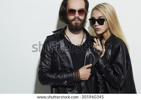 fashion beautiful couple in black leather wearing trendy glasses and posing together. Hipster boy and girl. Bearded young man and blonde in sunglasses - stock photo