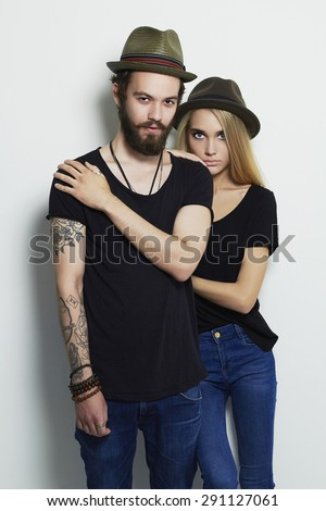 fashion beautiful couple in hat and posing over white background together. Hipster boy and girl. Bearded young man and blonde. Tattoo - stock photo