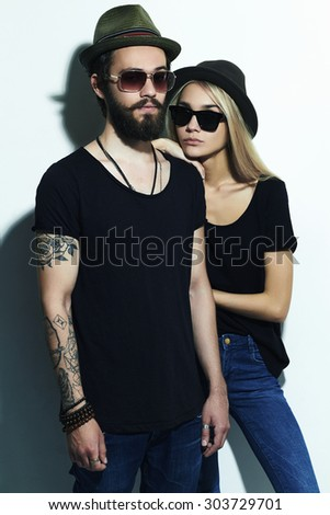 fashion beautiful couple in hat together. Hipster boy and girl. Bearded young man and blonde in sunglasses. tattoo and jeans - stock photo