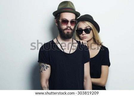 fashion beautiful couple in hat together. Hipster boy and girl. Bearded young man and blonde in sunglasses. tattoo. - stock photo