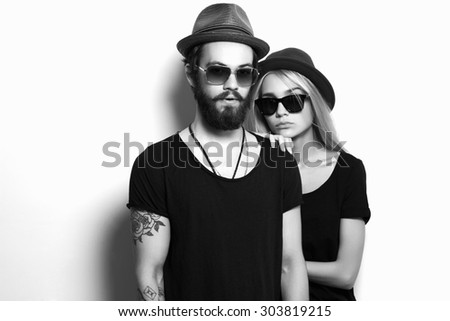 fashion beautiful couple in hat together. Hipster boy and girl. Bearded young man and blonde in sunglasses. tattoo. black and white portrait - stock photo