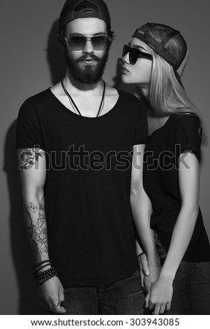 fashion beautiful couple in hat together. Hipster boy and girl in love. Bearded young man and blonde in sunglasses. tattoo. black and white portrait - stock photo