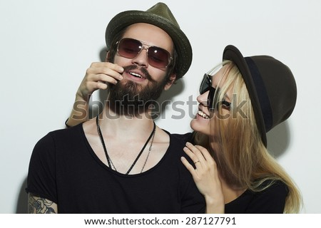 fashion beautiful happy couple in hat wearing trendy glasses together. Hipster boy and girl. Bearded young man and blonde in sunglasses - stock photo