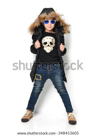Fashion beautiful little boy in blue winter clothing jacket jeans and sunglasses standing smiling over white background - stock photo