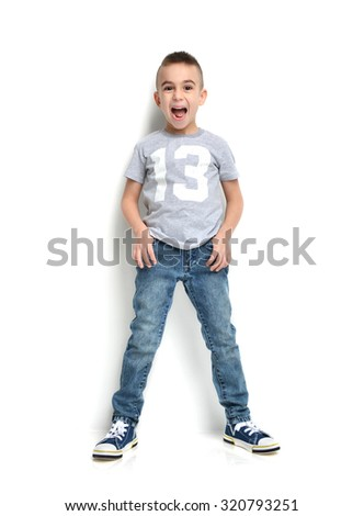 Fashion beautiful little boy in t-shirt 13 jeans standing and happy laughing over white background - stock photo