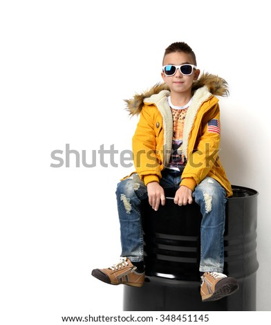 Fashion beautiful little boy in yellow winter clothing jacket jeans and sunglasses sitting over white background - stock photo