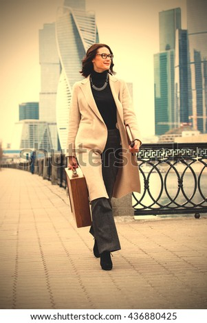 fashion. beautiful middle-aged woman with a wooden case in his hand in the bright coat walking along the embankment and smiling. instagram image filter retro style