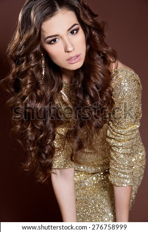 Fashion beautiful sensual woman with dark hair and jewelry. Beautiful woman with long curly hair - stock photo