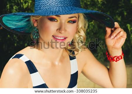 Fashion beautiful woman sunbathing on a chaise lounge near pool outdoors.  - stock photo