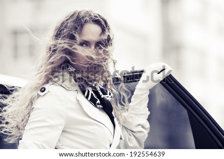 Fashion beautiful woman with long curly hairs at the car - stock photo